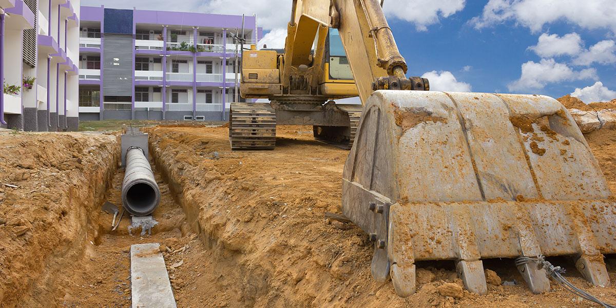 Backhoe preparing to bury an underground water main